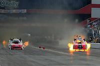 Jun. 19, 2011; Bristol, TN, USA: NHRA funny car driver Cruz Pedregon (right) has a fire alongside Bob Tasca III during eliminations at the Thunder Valley Nationals at Bristol Dragway. Mandatory Credit: Mark J. Rebilas-