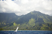 Man sailing a catamaran in Hanalei Bay, with Namolokama Mountain in the background