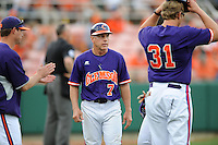 Head Coach Jack Leggett #7 talks with players during a pitching change in a  game against the Miami Hurricanes at Doug Kingsmore Stadium on March 31, 2012 in Clemson, South Carolina. The Tigers won the game 3-1. (Tony Farlow/Four Seam Images).