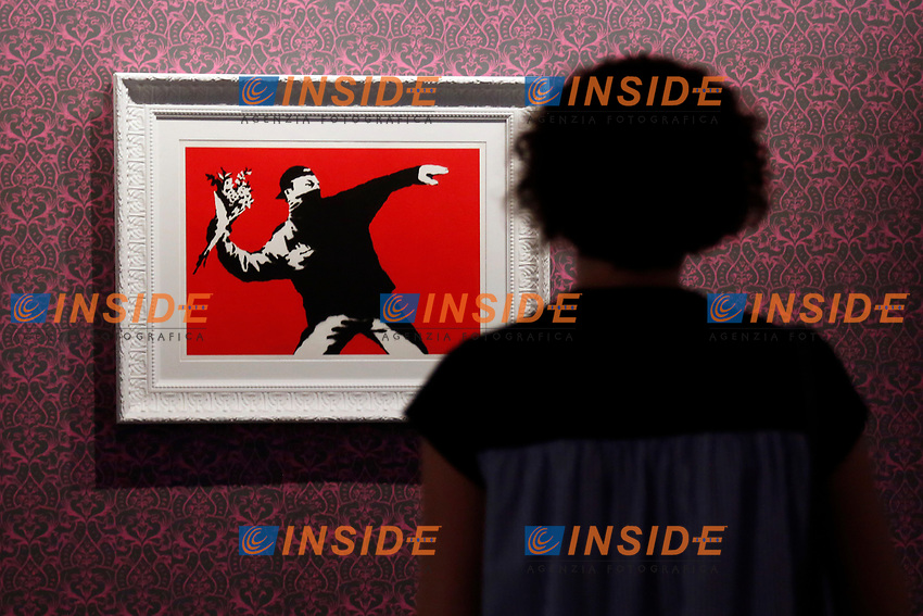Exhibition of the artist Bansky, titled A visual Protest, at Chiostro del Bramante in Rome. In the picture the painting Love is in the air - the flower thrower<br /> Rome (Italy), September 10th 2020<br /> Photo Samantha Zucchi Insidefoto