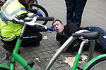© Joel Goodman - 07973 332324 . 06/04/2017 . Manchester , UK . A paramedic tends to a man , believed to have consumed spice , as he lies on the pavement and vomits , on Piccadilly Gardens . An epidemic of abuse of the drug spice by some of Manchester's homeless population , in plain sight , is causing users to experience psychosis and a zombie-like state and is daily being witnessed in the Piccadilly Gardens area of Manchester , drawing large resource from paramedic services in the city centre . Photo credit : Joel Goodman