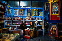 Local Bhutanese women, one dressed in jeans and the other one in traditional Bhutanese dress are seen sitting in front of the heater in a handicrafts store in the capital Thimpu, Bhutan.