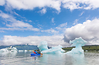 Packrafter paddles by icebergs in the Grand Plateau lake and glacier, Glacier Bay National Park, Southeast, Alaska