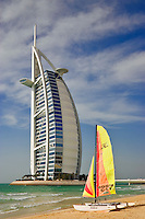 Burj al Arab Hotel, an icon of Dubai built in the shape of the sail of a dhow, stands on an artificial island just off Jumeirah Beach.  A sailboat has been pulled up onto the beach.  Dubai. United Arab Emirates.  Architects W.S. Atkins