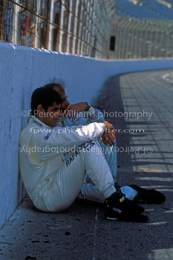 """Domenico """"Mimmo"""" Schiattarella (front) and Emanuele Pirro sit in the shade of the front straight wall before the start."""