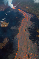 Aerial view of Kilauea Volcano east rift zone erupting hot lava from Fissure 8 in the Leilani Estates subdivision near the town of Pahoa. The lava drains downhill as an incandescent river to Kapoho, Big Island, Hawaii, USA