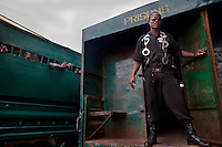 A guard stands at the rear of a prison van taking inmates from Pademba Prison to court. Every morning dozens of inmates from the prison are taken to court for trial. Many of them will need to go a number of times before the court reaches a final decision. They will be remanded in prisons during the years before sentencing.