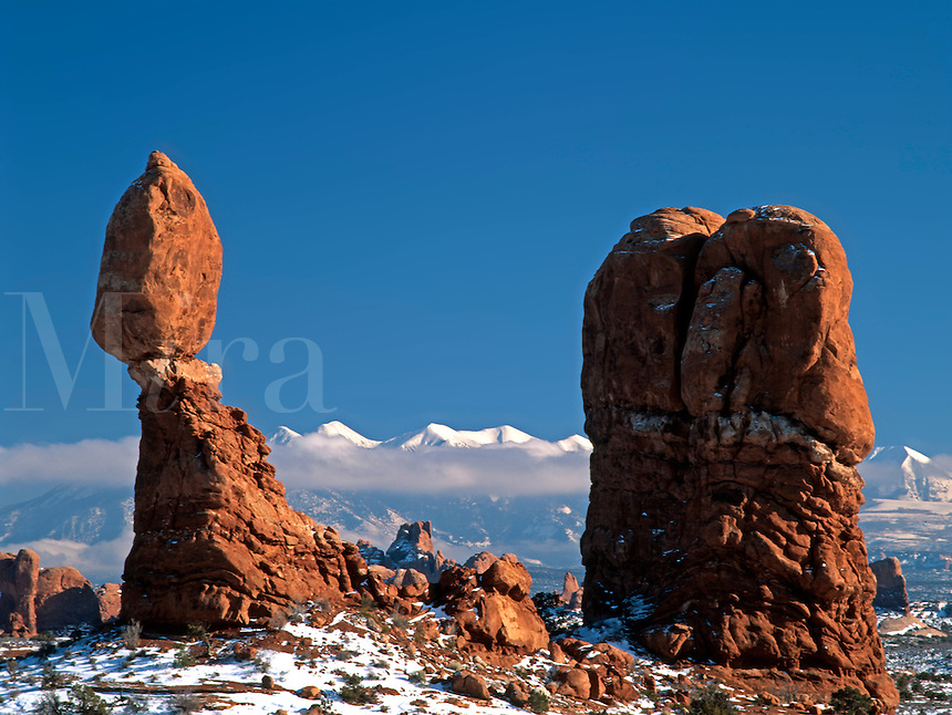 Balanced Rock rises over the Windows Section of Arches National Park in this winter time photograph with the snow capped La Sal Mountains in the background.<br />