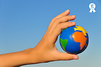 Hand holding small Earth Globe on blue sky (Licence this image exclusively with Getty: http://www.gettyimages.com/detail/103301314 )