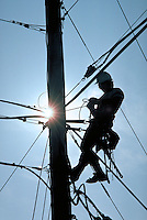 Silhouette of a Utility line worker on a pole, occupations, telecommunications.