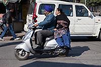 India, Dehradun.  A Sikh Man and Woman Riding a Motorbike--Wearing a Turban but no Helmet.