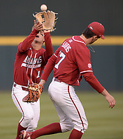 Arkansas second baseman Robert Moore (left) catches a fly ball Friday, April 2, 2021, as first baseman Brady Slavens avoids a collision during the fourth inning of play against Auburn at Baum-Walker Stadium in Fayetteville. Visit nwaonline.com/210403Daily/ for today's photo gallery. <br /> (NWA Democrat-Gazette/Andy Shupe)