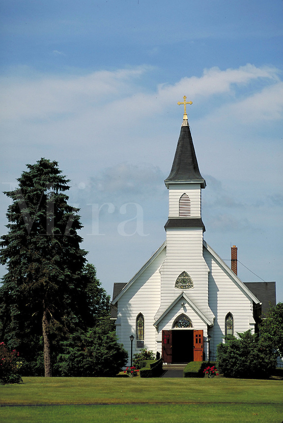 Small white church across wide green lawn. Square steeple with gold cross. Slender Gothic arch stained glass windows flank open doors; wider arched windows in pediment and steeple tower. Similar louvered opening high on steeple. Pomfret Connecticut USA Ne
