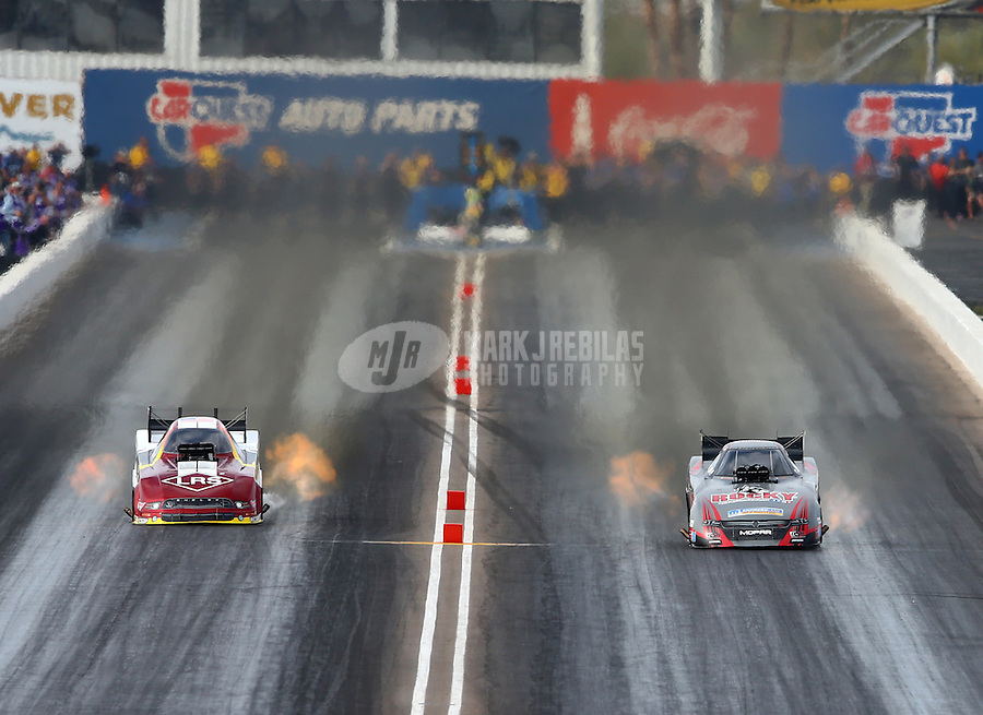 Feb 21, 2015; Chandler, AZ, USA; NHRA funny car driver Matt Hagan (right) races alongside Tim Wilkerson during qualifying for the Carquest Nationals at Wild Horse Pass Motorsports Park. Mandatory Credit: Mark J. Rebilas-