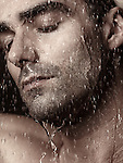Sensual closeup portrait of a man face with closed eyes under pouring rain or shower water Image © MaximImages, License at https://www.maximimages.com