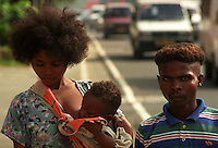 An Aeta family begs along Roxas Boulevard in Manila. Aetas are pygmy tribes endemic to the Philippines. They usually come down from the mountains where they live and endure the travel to big cities to beg for alms during the Christmas season. Ermita, Manila. December, 2002