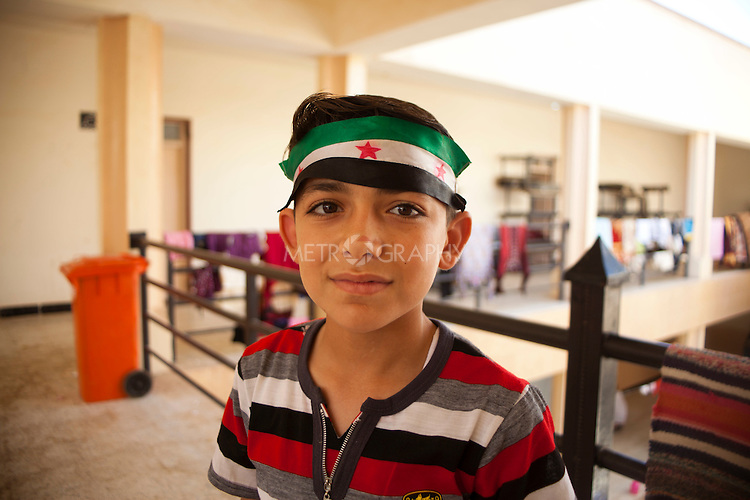 QAIM, IRAQ: A boy with the Syrian flag tied around his head stands in a disused building at the Qaim refugee camp in Iraq...Over 4,450 Syrian refugees have fled the violence in Syria and are living in the Qaim refugee camp in Iraq...Photo by Ali Arkady/Metrography
