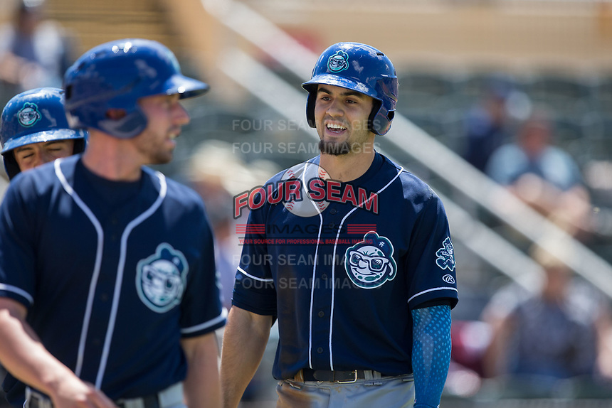 Willie Abreu (right) of the Asheville Tourists is all smiles as he returns to the dugout after hitting a home run against the Kannapolis Intimidators at Kannapolis Intimidators Stadium on May 7, 2017 in Kannapolis, North Carolina.  The Tourists defeated the Intimidators 4-1.  (Brian Westerholt/Four Seam Images)