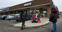 Santa Claus, portrayed by Santa Clarence, a member of the Amalgamated Order of Bearded Santas, sits with a few friends outside a shipping store where he greeted young and old to hear their Christmas wishes.
