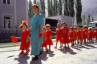 School parade in Khorog on the M41 highway in Tadzhikistan..The M41 Highway from the Ismaili capital of Khorog to the south capital of Kyrgyzstan - Osh, via the head district of Badakhshan - Murgab and the Akbajtal Pass at 4655 meters.