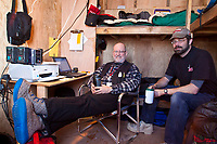 Communications volunteers Grant Jacobson (L) and Mike Holland in their 10' x 12'  Comm Shack/living quarters at the Cripple checkpoint during the 2010 Iditarod