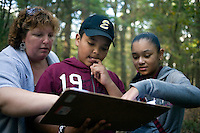 History teacher Dina Capalli (spelling unsure, left) helps Nelson Torres, 11, (center) and Dayla Olivo, 11, read a trail map as sixth grade students from Roger Williams Middle School in Providence, Rhode Island, walk along a trail at the Powder Mill Ledges Wildlife Refuge in Smithfield, Rhode Island, on Oct. 20, 2011. The students are part of the EcoExplorer program run by the Providence After School Alliance, which helps to kids in learning environments outside of school time.  The students make a weekly visit to the refuge, operated by the Rhode Island Audubon Society, to learn about nature and ecology.<br /> <br /> <br /> M. Scott Brauer for Education Week