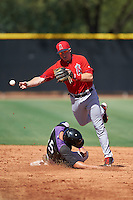 Los Angeles Angels of Anaheim Connor Justus (33) throws to first over a sliding Dom Nunez (5) during an Instructional League game against the Colorado Rockies on October 6, 2016 at the Tempe Diablo Stadium Complex in Tempe, Arizona.  (Mike Janes/Four Seam Images)