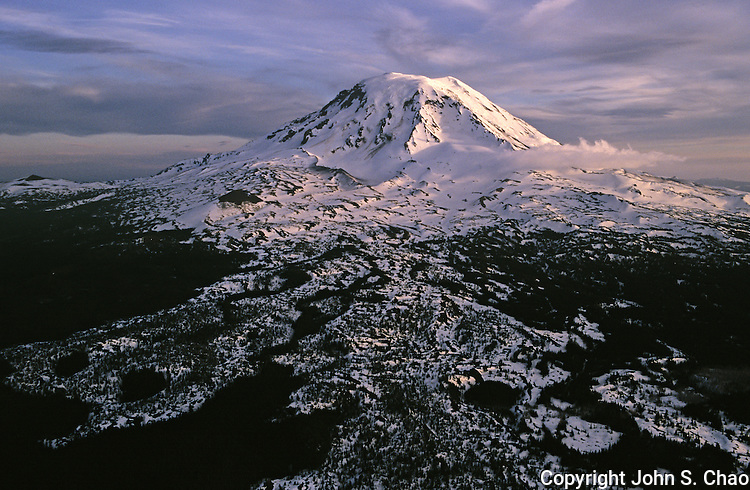 Aerial view of the northwest aspect of Mount Adams at 12,276 feet in elevation. Photographed with late afternoon light in winter. Ice and snow outline ancient lava flows emanating from this massive volcano in Washington State. Cloud formations above the summit suggest a volcanic plume.....35mm format on Velvia 100 film.