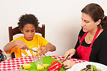 8 year old boy at home with mother in kitchen squeezing lemon as she cuts vegetables for salad