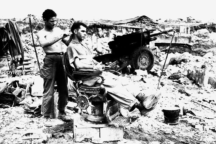 Pfc. Troy Dixon, Leadhill, Ark., uses a Japanese barber chair to cut the hair of Sgt. John Anderson, Anita, Pa.  Both men are members of the 363rd F.A. Bn., located near Shuri, Okinawa, June 10, 1945.  Hendrickson.  (Army)<br /> NARA FILE #:  111-SC-208582<br /> WAR & CONFLICT BOOK #:  928