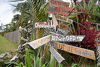 A directional sign stand featuring international to local destinations and distances is seen along Hana Highway, Maui.