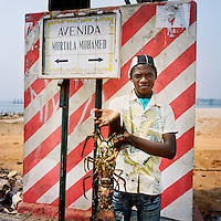 A young man offers a lobster for sale on Avenida Murtala Mohamed, the road that leads to the Ilha de Luanda..