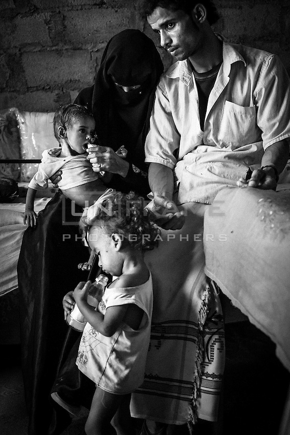Hend feeds her malnourished one year old daughter Rahaf with a plumpy nut, a fortified nutrition ration given by an NGO that operates in the area. Mohannad (2) is Rahafs brother. Hend gave him birth when she was 16 years old. Her husband, Fahman Salim (22), earns money as a taxi driver with a motorcycle which borrows from a friend for a few dolars a day. Attorba village<br /> <br /> October 10th 2012.