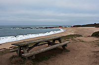 An empty picnic table with a view of a public beach on California's coast near San Francisco.