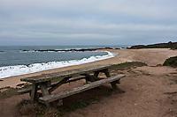 An empty picnic table with a view of a public beach on California's coast near San Francisco.