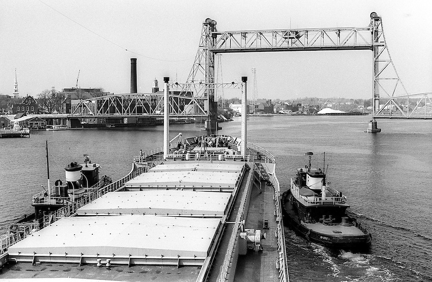 Tug boats assist large tankers and freighters traverse the fast flowing Piscataqua River at Portsmouth,New Hampshire. As of  2012, this bridge has been removed and a new bridge is under construction.Photograph by Peter E. Randall