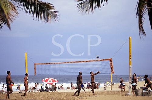Rio de Janeiro, Brazil. Young men playing volleyball on Copacabana beach.