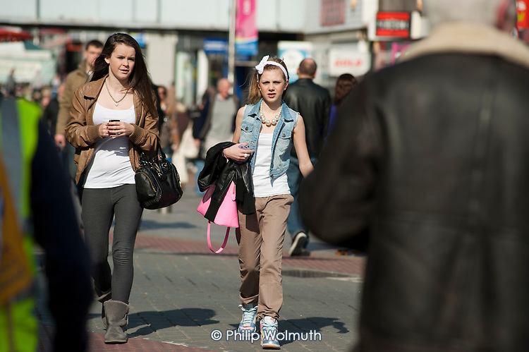 Two teenage girls walk in the High Street, Southend, Essex.