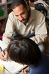 Education preschool 3-5 year olds male teacher working with boy discussing artwork journal