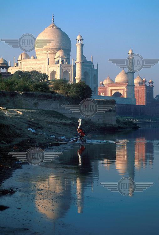india, Uttar Pradesh, Agra..Dhobi wallah washing clothes on stones in Yamuna River below the Taj Mahal, in early morning light...Mark Henley