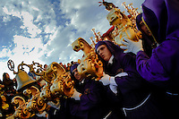 The gold-coated throne with the Paso scene on the top is carried on the shoulders of the carriers during the Easter celebration in Malaga, Spain, 3 April 2007.