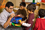 Preschool New York City ages 4-5 high school male volunteer interacting with group of boys in dressup pretend play area horizontal