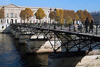 People crossing the Pont des Arts over the Seine, Paris, France.
