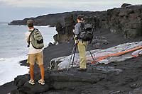 Photographers, Lava flows over a black sand beach towards the ocean, TEB, Thanksgiving Eve Breakout flow, West Waikupanaha lava ocean entry, Kilauea volcano, East of Hawaii, USA Volcanoes National Park, The Big Island of Hawaii, USA
