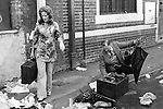 Man scavenging for radio parts and a well dressed woman with a suitcase she has just found.  Brick Lane, east London. England.  July 1978.