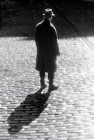 Silhouetted man standing on cobblestone street in the rain<br />