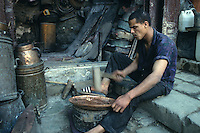 Fez, Morocco - Metal Worker Muhamad Fizazi Hammers a Metal Tray into Shape, in the Seffarin Square.