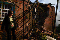 A woman gathers her belongings through the rubble of her house struck by shelling. Slovyansk, Ukraine.