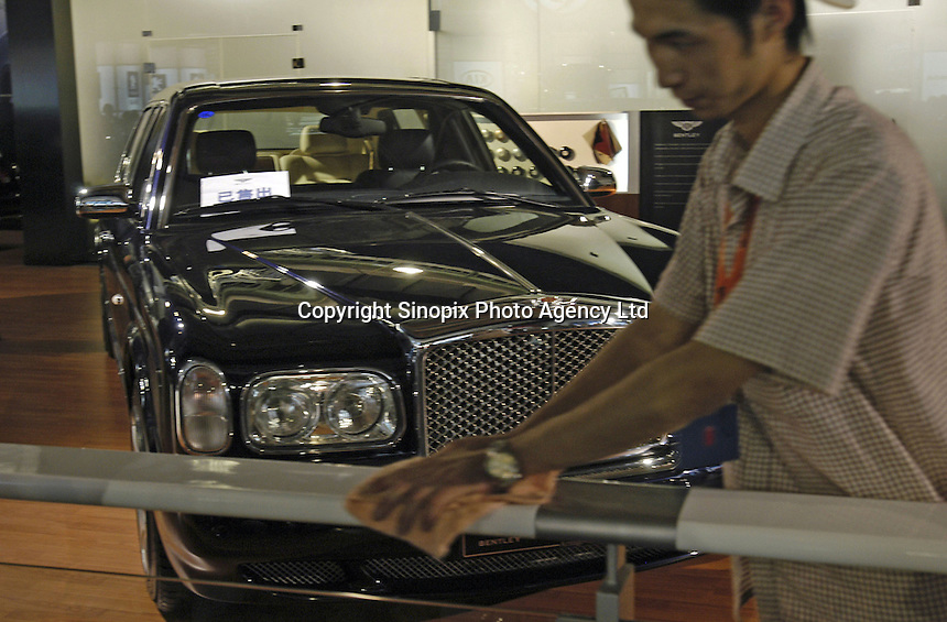A cleaning man wipes handrail in front of a Bentley Arnage-728 at the Auto China 2004 exhibition in Beijing, China..