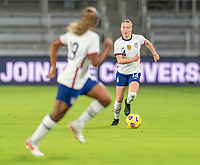 ORLANDO, FL - JANUARY 22: Emily Sonnett #14 passes the ball to Catarina Macario #29 of the USWNT during a game between Colombia and USWNT at Exploria stadium on January 22, 2021 in Orlando, Florida.